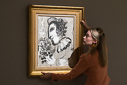 Bonhams, London, February 27th 2017. A member of Bonhams staff adjusts the hanging of Marc Chagall's 'Clown au bouquet de fleurs', which is expected to sell for between £100,000 and £150,000, at the Bonhams impressionist and modern art sale press preview at their Mayfair gallery in London.