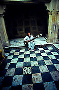 An Indian musician practices the sitar in a temple courtyard in Varanasi, India.