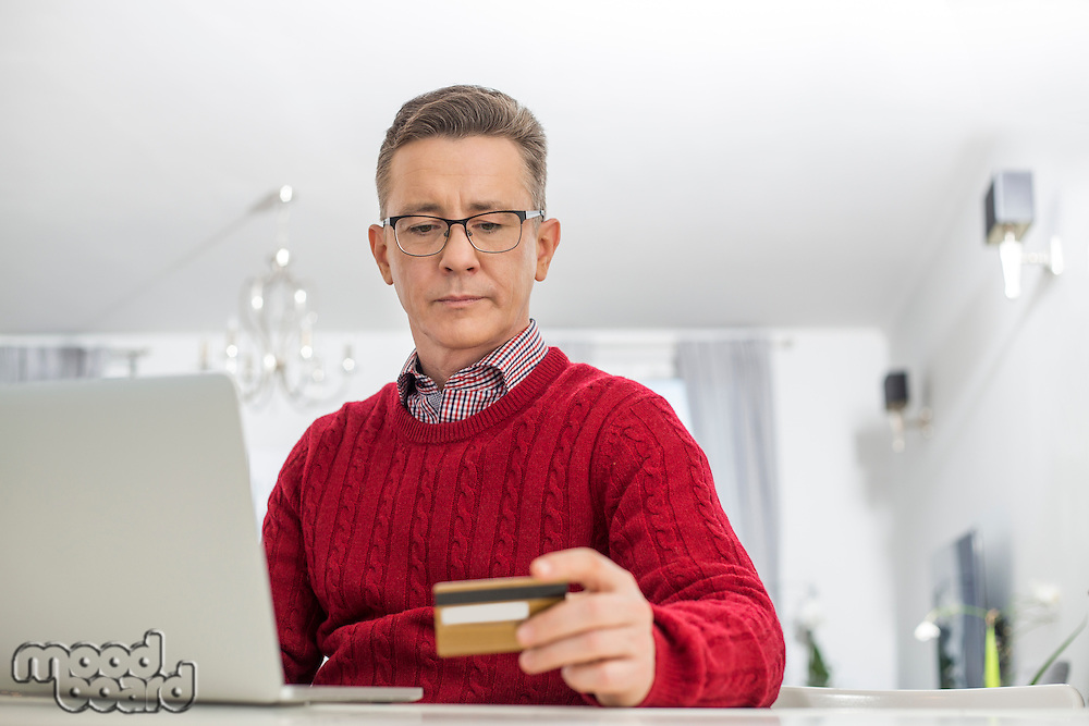 Mature man using credit card and laptop to shop online at home
