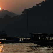 Wooden boats with tourists out to enjoy the sunset on the Mekong River near Luang Prabang, Laos.