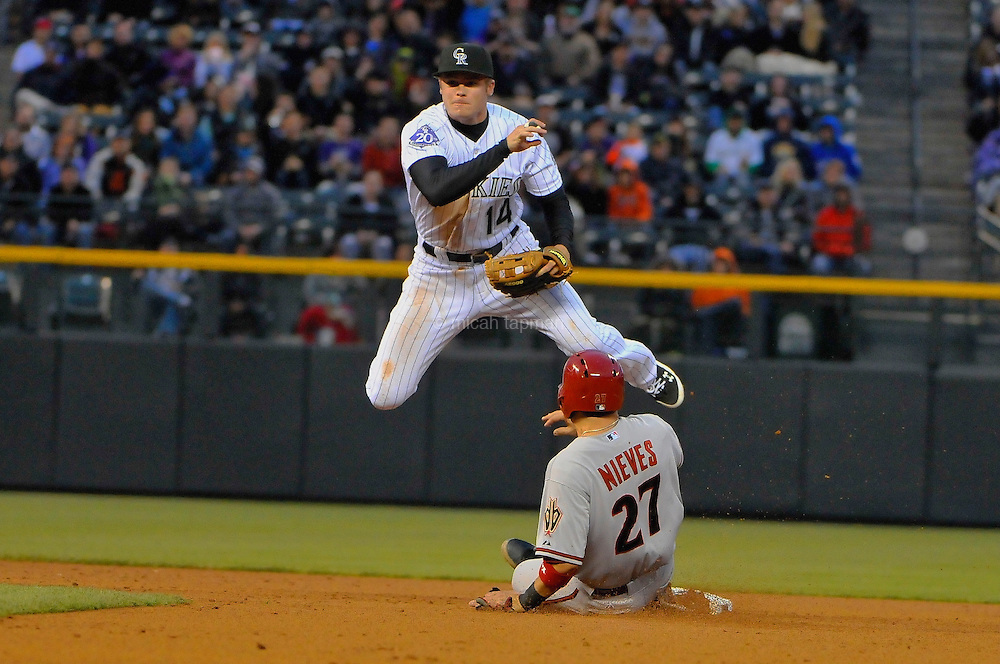 Josh Rutledge of the Colorado Rockies avoids a takeout slide by Wil Nieves of the Arizona Diamondbacks