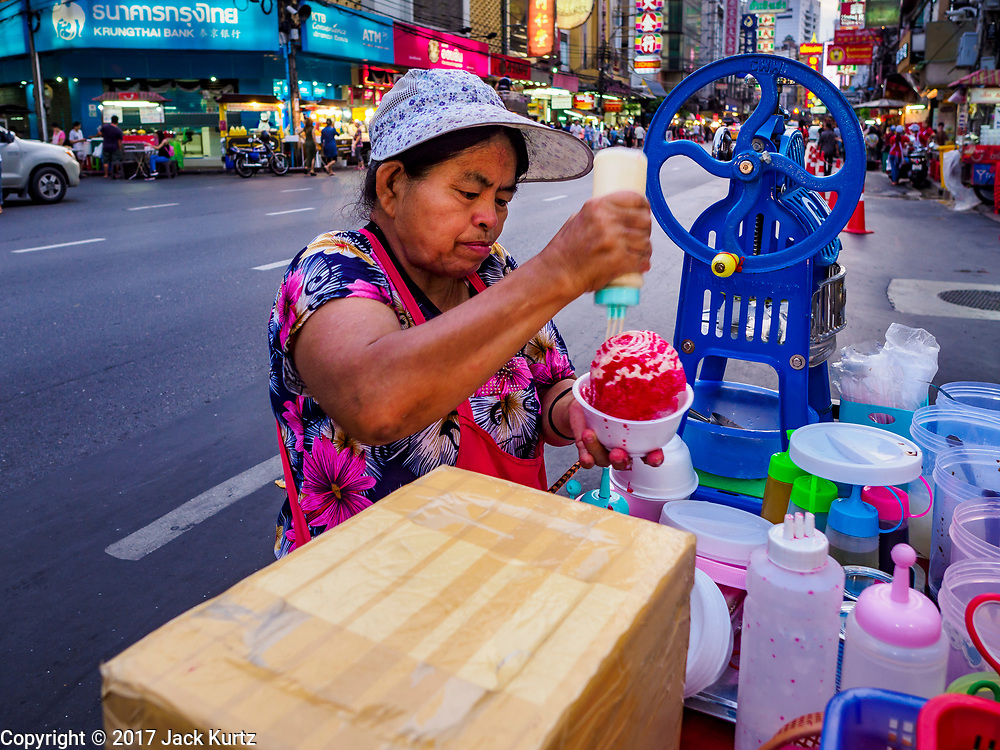 "18 MAY 2017 - BANGKOK, THAILAND: A dessert vendor makes a crushed ice dessert with coconut milk and sugar syrup on her mobile cart on Yaowarat Road in Bangkok. City officials in Bangkok have taken steps to rein in street food vendors. The steps were originally reported as a ""ban"" on street food, but after an uproar in local and international news outlets, city officials said street food vendors wouldn't be banned but would be regulated, undergo health inspections and be restricted to certain hours on major streets. On Yaowarat Road, in the heart of Bangkok's touristy Chinatown, the city has closed some traffic lanes to facilitate the vendors. But in other parts of the city, the vendors have been moved off of major streets and sidewalks.      PHOTO BY JACK KURTZ"