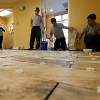 Thomas Wells | Buy at PHOTOS.DJOURNAL.COM<br /> Tupelo fire fighters Sidney Jones, from left, Jamie Roberts, Cpt. Justin Lamb and T.K. Hollingsworth continue to put down a new tile floor in the Fire Station #4 on North Gloster on Wednesday.