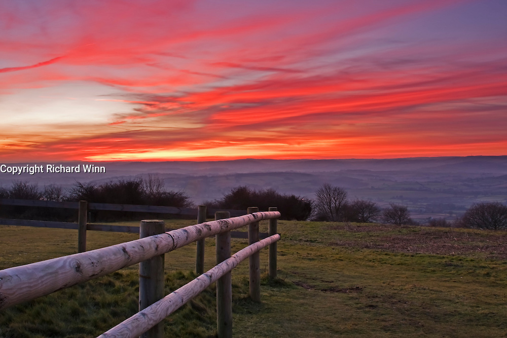 View from Cothelstone Hill on the Quantocks, of the sunset over the Brendon Hills to the West, with a fence in the foreground as a leading line.