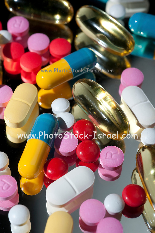 an assortment of pills and capsules on black background