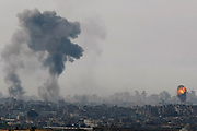 Smoke rises over a bombed building in Gaza during an Israeli air strike against Hamas targets on December 27<br />