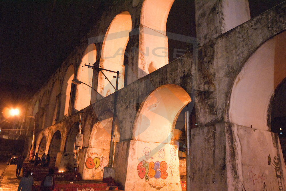 the lapa arches at night were built as an aqueduct originally, but now carry travelers on a tram between centro and santa teresa rio de janeiro, brazil.