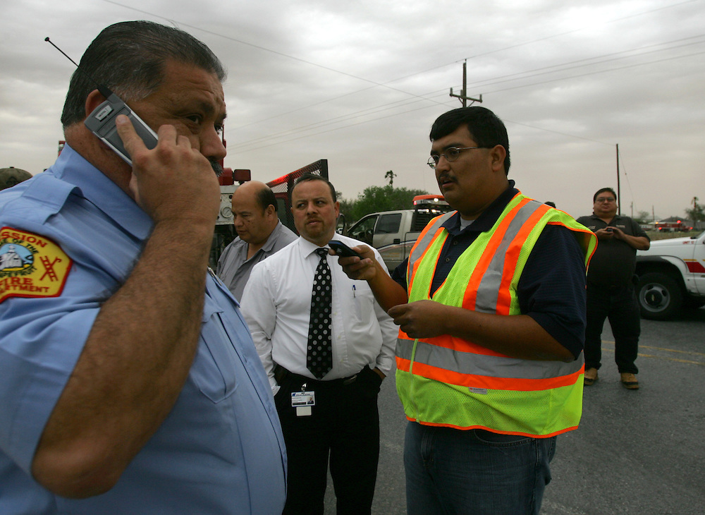 "San Isidro, TX - 18 Mar 2008 -.Incident commander Domingo ""Mingo"" Hinojosa (right) plans an attack on the fire as Mission Fire department chief Ricardo Saldaña gives an order by phone on FM 755 outside San Isidro on Tuesday afternoon..Photo by Alex Jones / ajones@themonitor.com"