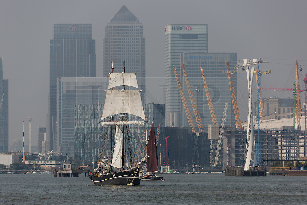 © Licensed to London News Pictures. 15/06/2016. LONDON, UK.  The historic tall ship, Jantje passes through the Thames Barrier, in front of Canary Wharf and the O2 on the River Thames. The Sail Royal Greenwich Tall Ship Festival runs until this Sunday, 18th Septmeber.  Photo credit: Vickie Flores/LNP