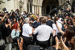 © Licensed to London News Pictures. 24 07 2020. London, UK. Photographers, security guards and fans swarm around actor JOHNNY DEPP, clutching flowers from a fan, as he arrives at the high Court in London Johnny Depp is in a legal dispute with The Sun, a UK tabloid, over allegations he assaulted his former wife, Amber Heard. Photo credit: Paul Davey/LNP