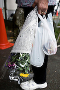 Visit by residents to homes in nuclear exclusion zone, Okuma, Fukushima Prefecture, Japan on Aug. 31 2011. Rob Gilhooly PhotoA resident carries flowers before boarding a bus that would transport her to her home inside the nuclear exclusion zone in Okuma, Fukushima Prefecture, Japan on Aug. 31 2011.  Residents were allowed briefly to return and collect valuables and other belongings from their home. Some residents who lost their homes in the March 11 disasters decided to take flowers to leave by the gravesides of deceased family members. Robert Gilhooly Photo