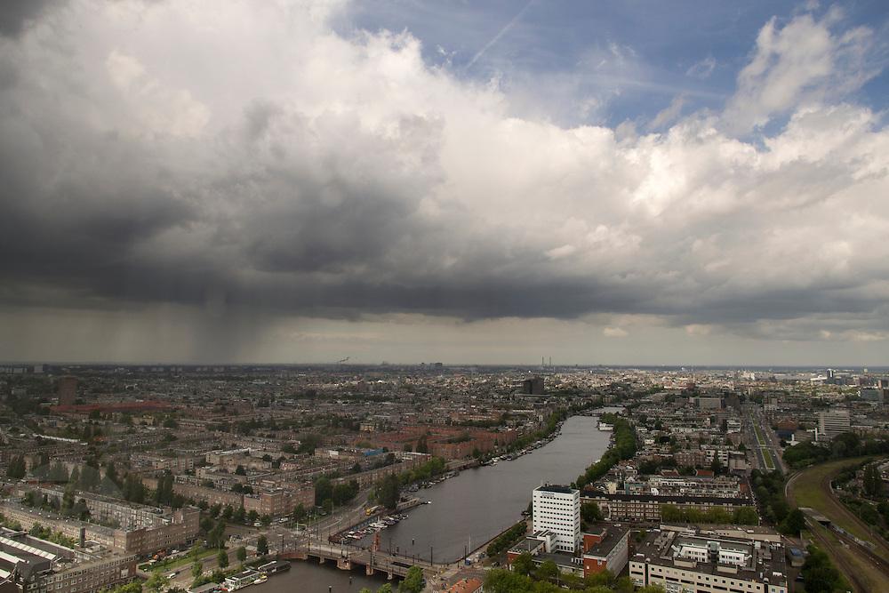 Uitzicht op Amsterdam, waar een regenbui valt, vanaf de Rembrandt-toren bij Amsterdam Amstel.<br /> <br /> Amsterdam form above, while rain is falling.