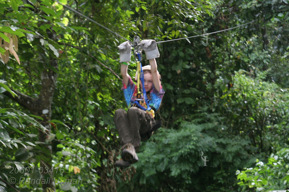 Ecoteach girl Kelsey Seibel (age 11) ziplines through Pacific coastal rainforest on the Monkey Trail Canopy Tour at Hotel Punta Leona, Costa Rica.