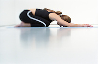 Woman relaxing in childs pose duringa yoga session.