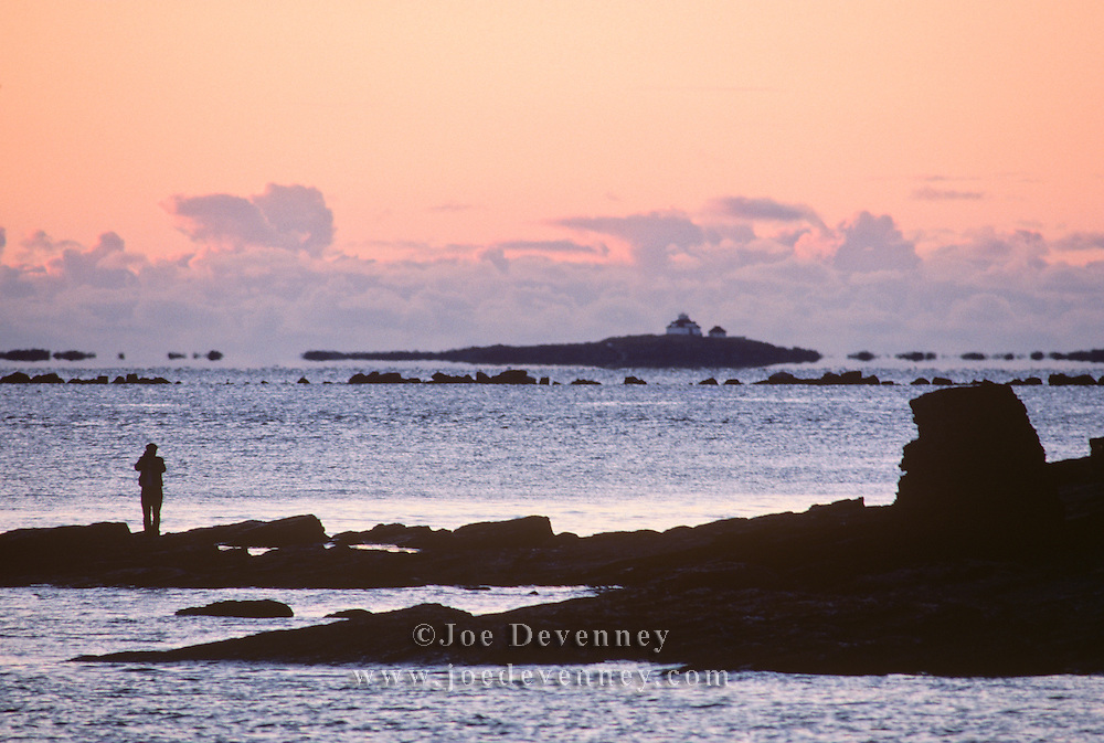 Person photographing the lighthouse on Duck Island in Acadia National Park at sunrise.
