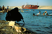 Suez, 1997 - Traditionally dressed woman feels the water. She will have to swim in all of her clothes while childen swim freely around her. A container ship loaded with cargo makes its way through the suez canal in the background.