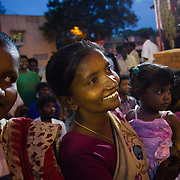 A woman smiles as she watches children dance during a celebration by Janodayam celebrating two high school students who achieved high grades. Saidapet, Chennai, India.