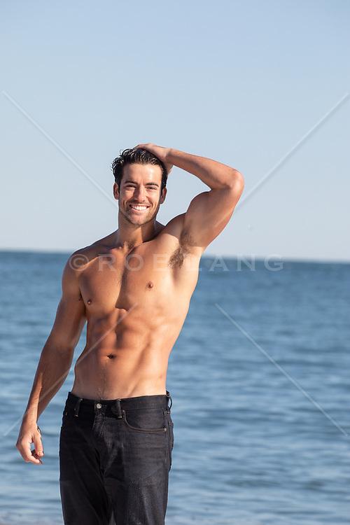 shirtless muscular man at the ocean smiling
