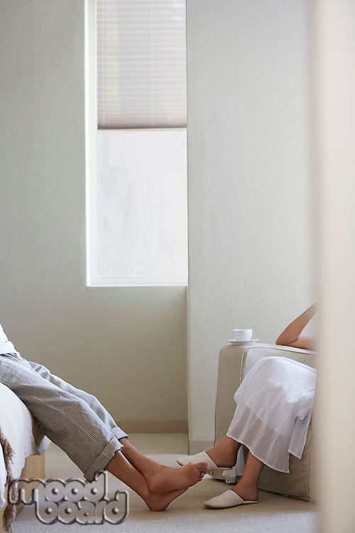 Couple relaxing sitting in bedroom low section