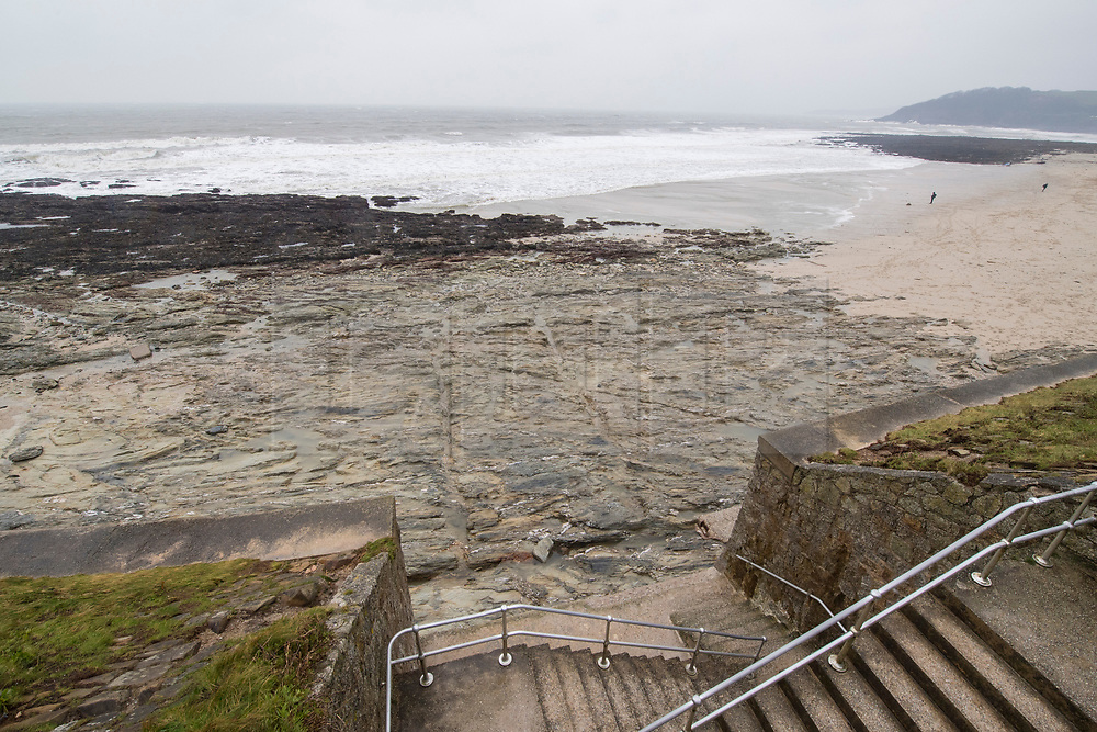 © Licensed to London News Pictures. 02/03/2018. FALMOUTH CORNWALL, UK. Beach has been washed away, now there are only rock where just yesterday there was beach sand. Storm Emma caused damage to the beaches and businesses of Falmouth at the morning high spring tide today. The strong wind and the spring tide caused a beach to be washed away at Gylly beach. At Swanpool beach the beach was washed onto the road causing it to be blocked .  Photo credit: MARK HEMSWORTH/LNP
