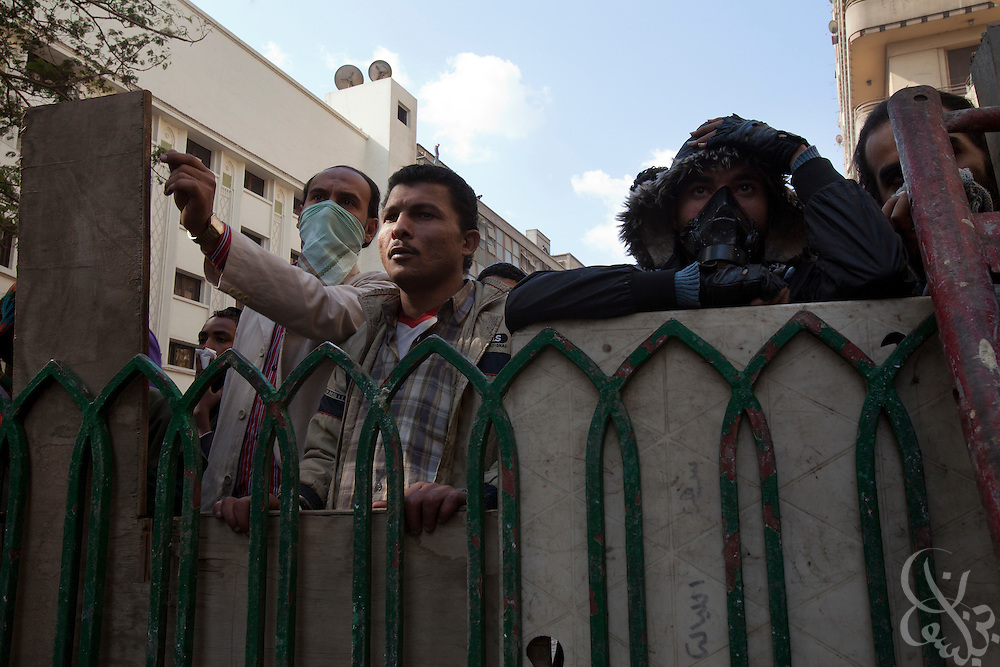 Egyptian protestors take cover behind makeshift barricades during street battles with security forces  November 21, 2011 near Tahrir square  in central Cairo, Egypt. Thousands of protestors demanding the military cede power to a civilian government authority clashed with Egyptian security forces for a third straight day in Cairo, with hundreds injured and at least 24 protestors killed.  (Photo by Scott Nelson)
