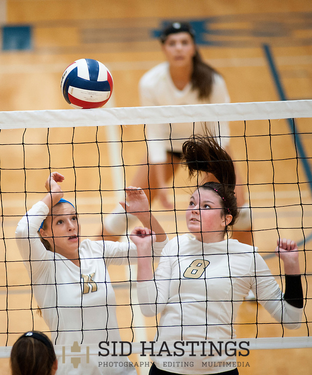 25 AUG. 2015 -- ST. CHARLES, Mo. -- St. Pius X High School volleyball players Elle Russell (11) and Emma Grimshaw (8) leap to block a shot by a Duchesne High School player during the match between the two schools at Duchesne in St. Charles, Mo. Tuesday, Aug. 25, 2015. St. Pius won, 2-0 (25-14, 25-23), to advance to 6-0. It was Duchesne's first match, dropping them to 0-1 on the year. Photo © copyright Sid Hastings.