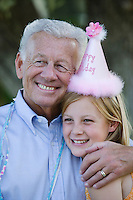 Senior man embracing granddaughter