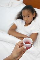 Hand holding medication for girl (7-9) lying in bed
