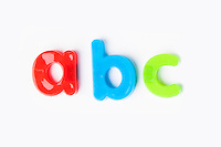 Colorful alphabet magnets spell 'a b c' over white background