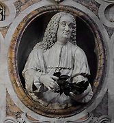 Bust of Bernardino Perfetti, 1681-1746, Italian jurist and poet, detail from the Perfetti Monument, in the Duomo di Siena or Siena Cathedral, built 1196-1348 and consecrated in 1215, designed by Giovanni di Agostino, Giovanni Pisano and Camaino di Crescentino, in Siena, Tuscany, Italy. Perfetti is shown holding the crown he received at the wedding of Charles Albert of Bavaria, which he presented to the Madonna del Voto in the Duomo. The cathedral has elements of Italian Gothic, Romanesque, and Classical styes and is built from stripes of white and green-black marble. The historic centre of Siena is listed as a UNESCO World Heritage Site. Picture by Manuel Cohen