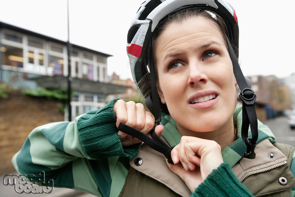 Young woman adjusting her helmet