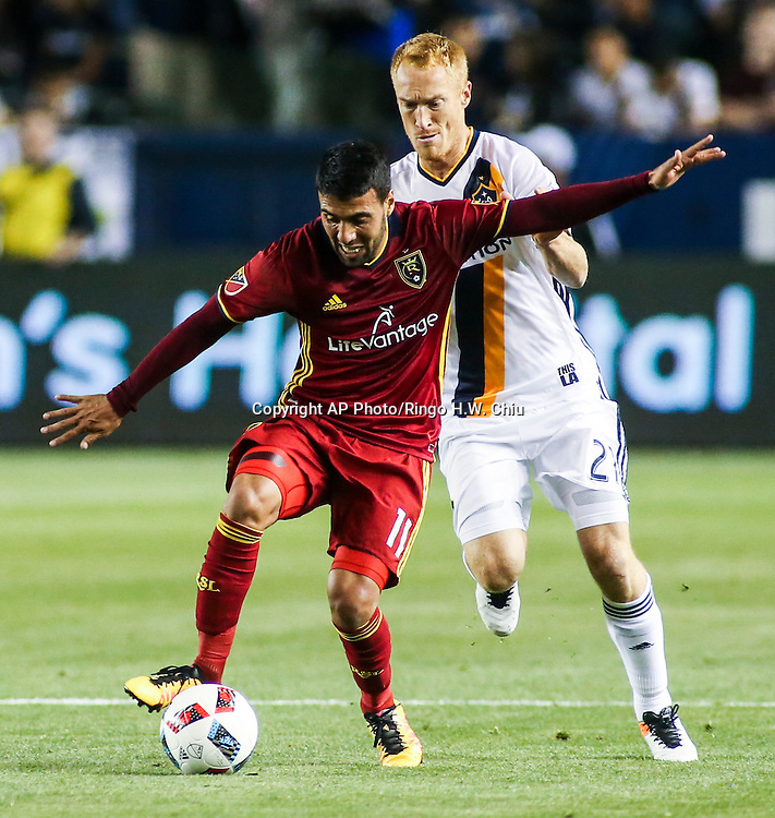 Real Salt Lake midfielder Javier Morales, left, controls the ball against Los Angeles Galaxy midfielder Jeff Larentowicz in the second half of an MLS soccer game in Carson, Calif., Saturday, April 23, 2016. The Galaxy won 5-2. (AP Photo/Ringo H.W. Chiu)