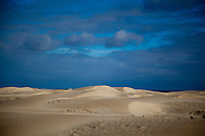 The sand dunes of Isla Magdalina in Baja, Mexico are lit dramatically by the rising sun with approaching storm clouds in the distance.