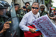 24 MAY 2014 - BANGKOK, THAILAND:  A anti-coup protestor scuffles with police at a police roadblock in Bangkok. There were several marches in different parts of Bangkok to protest the coup that unseated the popularly elected government. Soldiers and police confronted protestors and made several arrests but most of the protests were peaceful. The military junta also announced that firing of several police commanders and dissolution of the Thai Senate. The junta also changed its name from National Peace and Order Maintaining Council (NPOMC) to the National Council for Peace and Order (NCPO).   PHOTO BY JACK KURTZ