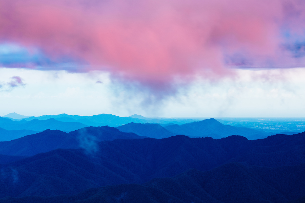 Pink contrasting clouds high above mountain ridges and valleys below from Point Lookout. New England National Park.