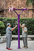 Elderly Chinese women exercise on a machine in the old French Concession of Shanghai, China