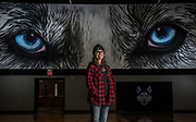 Cherie Ramsdell stands in front of her Husky eyes mural in the Bridgewater-Emery School gymnasium. Ramsdell completed two murals inside the school's gym. (Matt Gade / Republic)
