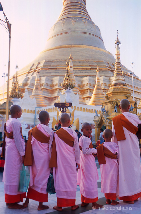 Young novice nuns. Shwedagon Paya, the most important Buddist temple in Rangoon. Nearly 100 metres high. Decorated with 8000 gold plates, 5000 diamonds and 2000 other precious and semi precious stones and surrounded by 82 smaller temples, attracts the faithful day and night.<br /> Rangoon, Burma. 1999