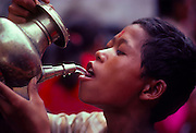 A Nepali boy drinks fresh water from a pitcher in the bazaar in Kathmandu