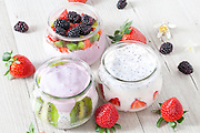 Bowls with different type of soft fruits yogurt: strawberry, blackbery and kiwi.