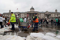 © Licensed to London News Pictures.07/04/2012. London, UK. Cleaners begin clearing away the remains of hundreds of pillows in Trafalgar Square.  Hundreds of people took part in 'International Pillow Fight Day' today (07/04) in Trafalgar Square. The event which has been running since 2010 happens in dozens of cities around the world.Photo credit : James Gourley/LNP
