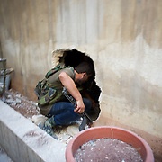 August 10, 2012 - Aleppo, Syria: A Free Syria Army (FSA) fighter advances towards the frontline through a hole in a wall of a house in Saheledine, a strategic neighborhood in southwest Aleppo...The Syrian Army have in the past week increased their attacks on residential neighborhoods where Free Syria Army rebel fights have their positions in Syria's commercial capital, Aleppo. (Paulo Nunes dos Santos/Polaris)