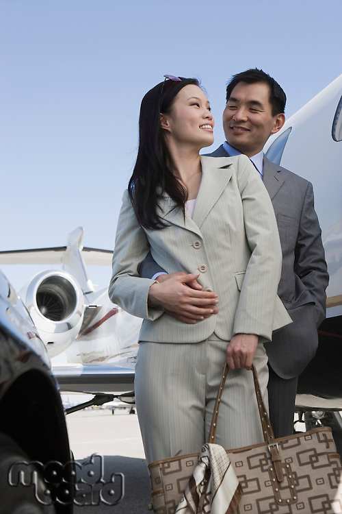 Mid-adult Asian business couple standing in front of car and airplane.