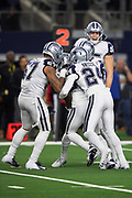 Dallas Cowboys outside linebacker Damien Wilson (57), Dallas Cowboys cornerback Chidobe Awuzie (24), and Cowboys teammates mob Cowboys cornerback Jourdan Lewis (27) after Lewis intercepts a late fourth quarter pass and runs it back 7 yards to the New Orleans Saints 16 yard line on the game winning turnover as the time clocks winds down during the NFL week 13 regular season football game against the New Orleans Saints on Thursday, Nov. 29, 2018 in Arlington, Tex. The Cowboys won the game 13-10. (©Paul Anthony Spinelli)