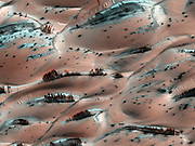 dark streaks of sediment on the downwind side of the dunes on the surface of Mars. They were created by escaping gas from the evaporating carbon dioxide ice below. The bottom of the ice melts into vapour and moves toward holes in the ice, carrying dark sediment along with it that is then deposited when the gas escapes. This image was taken by the High Resolution Imaging Science Experiment (HiRISE) camera on NASA's Mars Reconnaissance Orbiter in April 2008.