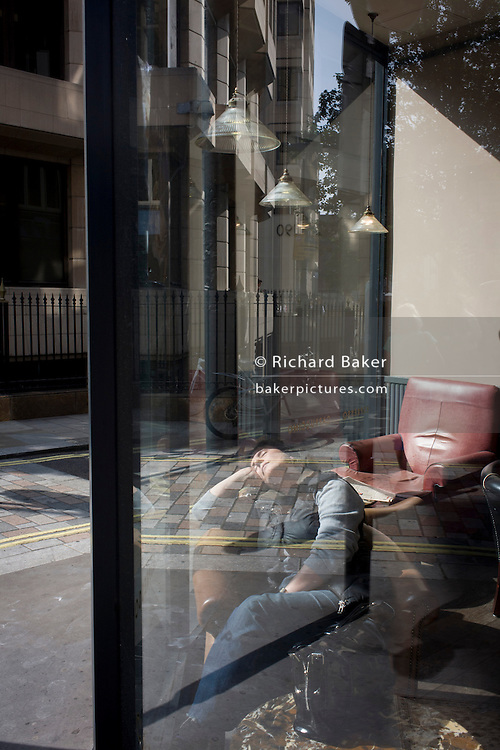 A woman sleeps in the warm sunshine in a window of Caffe Nero in central London.