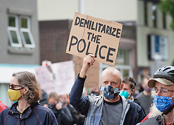 Many carrying signs, people march along a street during a June 7, 2020, Black Lives Matter protest in Eugene, Oregon. Participants were protesting the murder of George Floyd and other African-Americans by police. Most protesters wore masks because of the coronavirus pandemic.