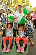 Garden City, New York, U.S. - June 6, 2014 -  Kelly of Garden City is with her 3 young daughters, who are holding green and white beach balls, at the 17th Annual Garden City Belmont Stakes Festival, celebrating the 146th running of Belmont Stakes at nearby Elmont the next day. There was street festival family fun with live bands, food, pony rides and more, and a main sponsor of this Long Island night event was The New York Racing Association Inc.
