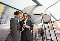 Businessman showing businesswoman PDA in front of revolving door low-angle view