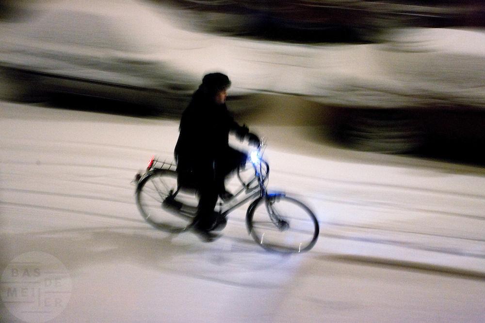 Een man rijdt op de fiets door de eerste sneeuw die van de winter van 2009/2010 is gevallen
